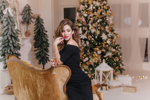 Mulher pensativa em um vestido preto longo, olhando para longe durante a celebração do ano novo. menina encaracolada relaxada posando no sofá marrom em frente a árvore de natal decorada.