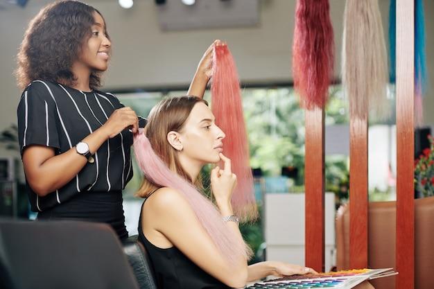 Mulher pensativa escolhendo extensões de cabelo