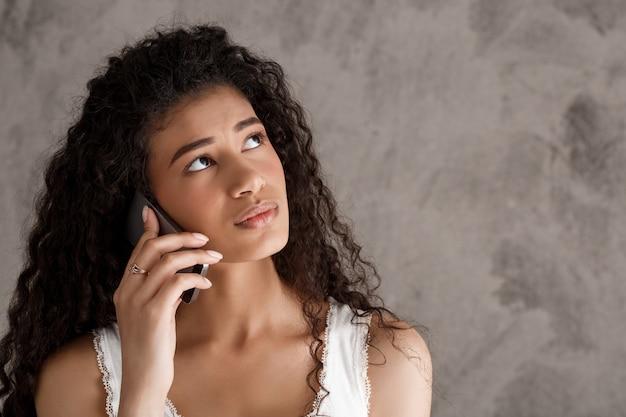 Mulher pensativa, falando no celular