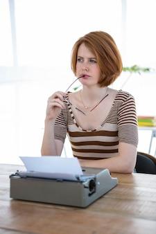 Mulher pensativa hipster, sentado em sua mesa com uma máquina de escrever