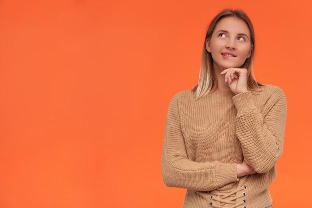 Mulher pensativa, jovem e atraente loira de cabelos curtos e cabeça branca mordendo o lábio inferior enquanto olha de lado sonhadoramente e apoiando o queixo na mão levantada, isolado sobre uma parede laranja
