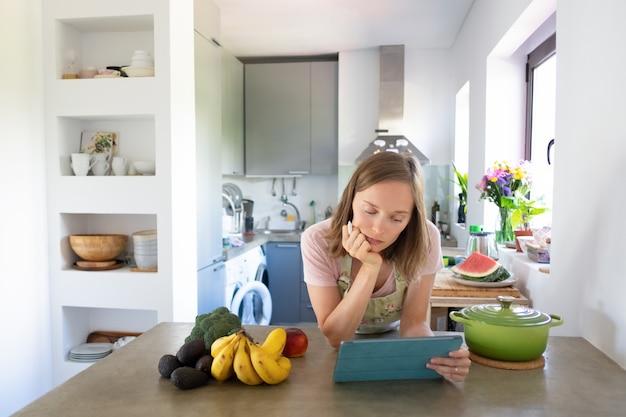 Mulher pensativa lendo receita no tablet enquanto cozinha na cozinha dela, assistindo a aula de culinária online. vista frontal. cozinhando em casa e conceito de alimentação saudável