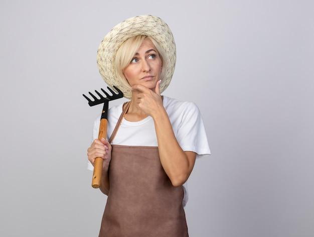Mulher pensativa, loira de meia-idade, jardineira, de uniforme, usando um chapéu, segurando o ancinho, mantendo a mão no queixo, olhando para o lado isolado na parede branca com espaço de cópia