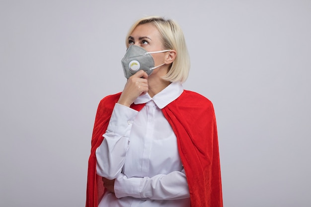 Mulher pensativa, loira, de meia-idade, super-heroína com capa vermelha e máscara protetora, colocando a mão no queixo, olhando para cima, isolada na parede branca com espaço de cópia