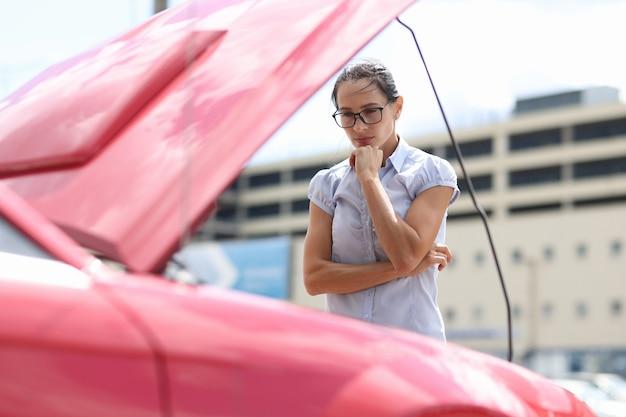 Mulher pensativa olha para a avaria do motor do carro no conceito de estrada