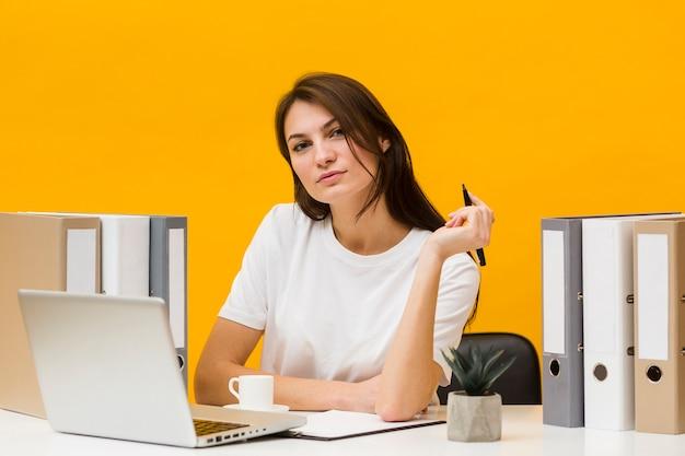 Mulher pensativa posando na mesa, segurando a caneta