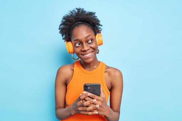 Mulher pensativa positiva com pele escura de cabelo encaracolado natural usa aplicativo de telefone celular ouve música
