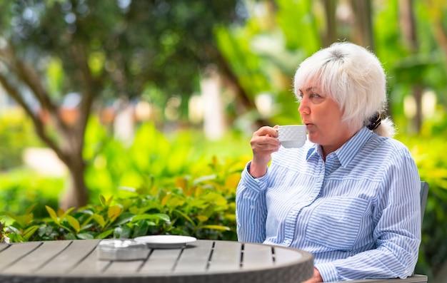 Mulher pensativa relaxando com uma xícara de chá ou café