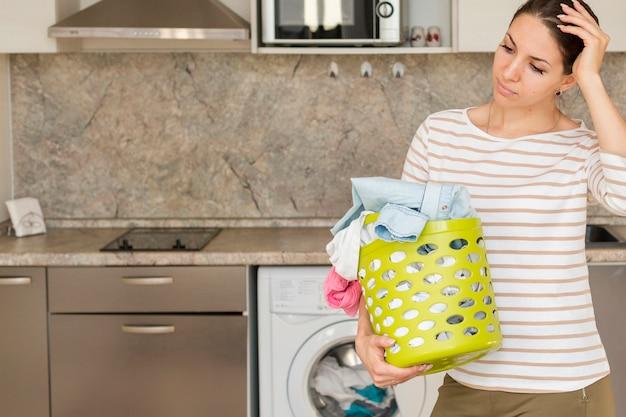 Mulher pensativa, segurando o cesto de roupa suja