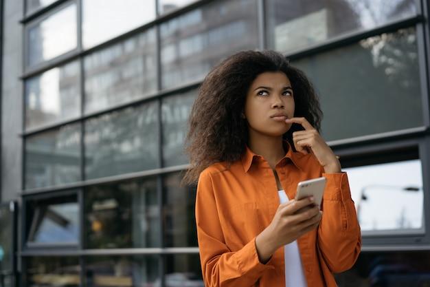 Mulher pensativa, segurando o smartphone, compras on-line. linda garota afro-americana esperando por táxi