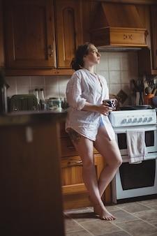 Mulher pensativa segurando uma xícara de café na cozinha