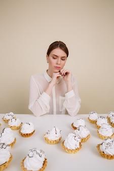 Mulher pensativa, sentada à mesa com bolos e pensando
