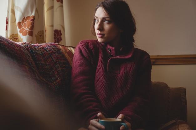 Mulher pensativa sentada e segurando uma xícara de café