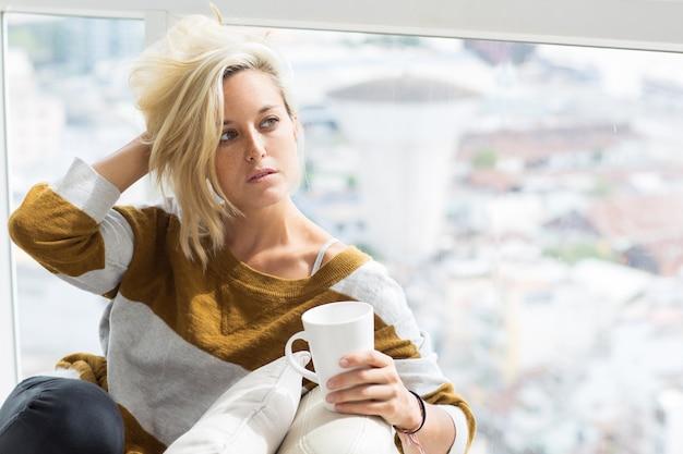 Mulher pensativa sentada em casa e cabelo despenteado