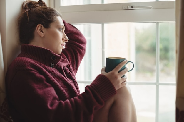 Mulher pensativa sentada no peitoril da janela segurando uma xícara de café