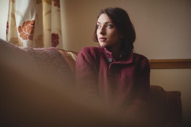 Mulher pensativa sentada no sofá da sala