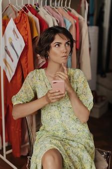 Mulher pensativa, sonhadora, com cabelos curtos e um vestido floral olha para cima