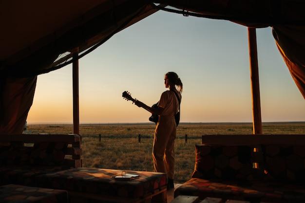Mulher pensativa tocando música gutiar sob uma enorme barraca de madeira, olhando o pôr do sol. bela estepe simples ao redor. de dentro da barraca, escuro, cores como silhueta.