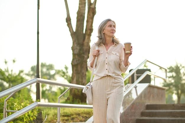 Mulher pensativa tomando café na escada do parque