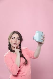 Mulher pensativa, tomando uma selfie no smartphone