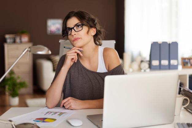 Mulher pensativa trabalhando em casa