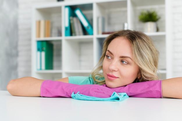 Mulher pensativa, usando luvas de borracha, apoiando-se na mesa branca, olhando para longe