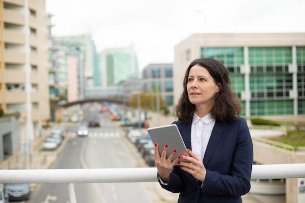 Mulher pensativa usando o tablet pc