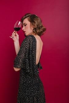 Mulher pensativamente de cabelos escuros posando com um copo de vinho na festa
