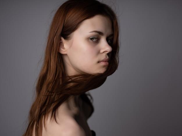Mulher penteado ombros nus pele clara moda fundo escuro. foto de alta qualidade