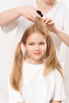 Mulher penteia e arruma o cabelo de uma menina em um fundo branco. a mamãe é cabeleireira. economizando dinheiro em um salão de beleza. shampoos e cosméticos para cabelos infantis.