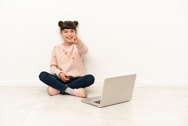 Mulher pequena com um laptop sentada no chão surpresa e apontando para a frente