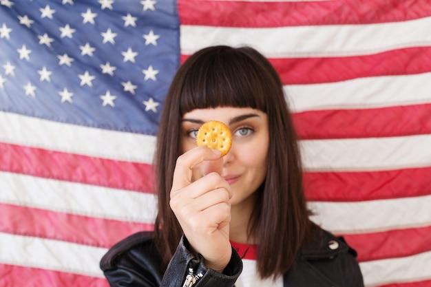 Mulher pequena ou adolescente vestida de hipster comendo poses com biscoito de manteiga de amendoim crocante, lanche tradicional americano típico com bandeira dos eua