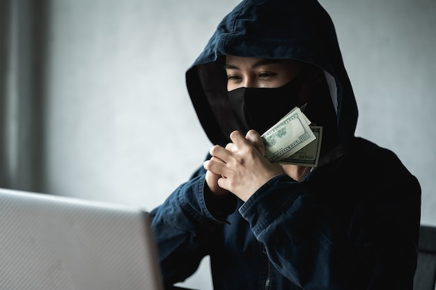 Mulher perigosa hacker com capuz segurou o dinheiro depois de hackear com sucesso.