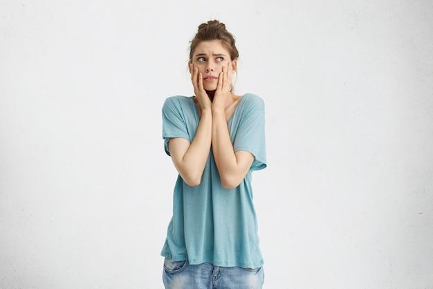 Mulher perplexa com os cabelos presos em um coque desviando o olhar, com expressão de frustração, segurando o rosto com as mãos, preocupada