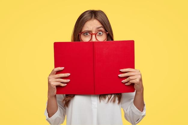Mulher perplexa de cabelos escuros levanta as sobrancelhas, olha perplexa sobre o livro vermelho, usa camisa branca, modela contra a parede amarela, aprende novas informações, prepara a tarefa de casa, lê a história