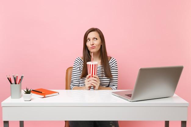 Mulher perplexa e perplexa, coaxando, pensando, olhando para cima, segurando um copo de plástico com coca-cola, refrigerante sentado, trabalhando na mesa branca com o laptop do pc