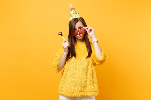 Mulher perplexa e perplexa no chapéu de aniversário, segurando óculos engraçados laranja com pé de cachimbo, celebrando isolado em fundo amarelo. conceito de estilo de vida de emoções sinceras de pessoas. área de publicidade.