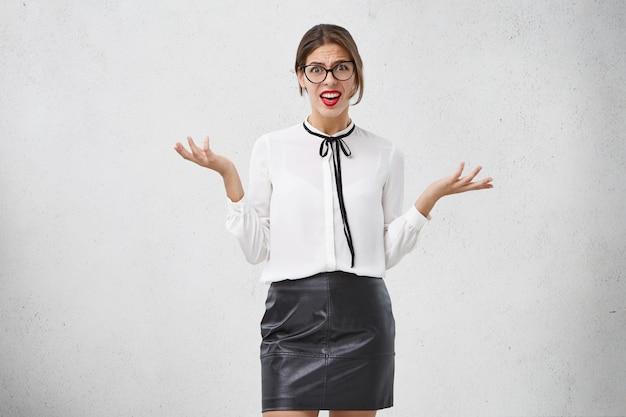 Mulher perplexa usa óculos, blusa e saia estilosos, faz gestos de perplexidade, tem olhar desagradável