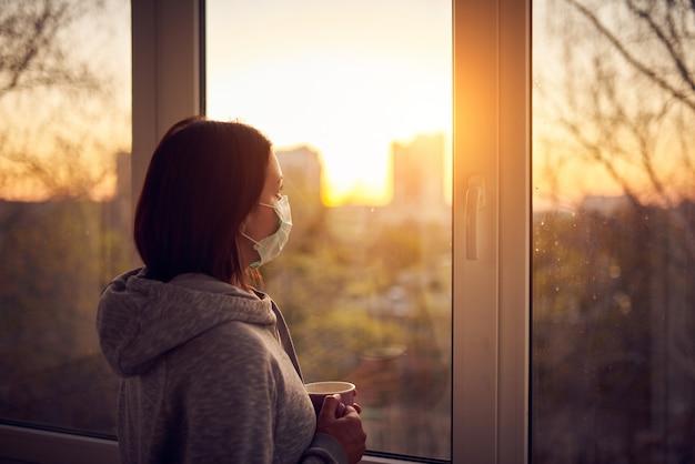 Mulher perto da janela ao pôr do sol em isolamento em casa para surto de vírus. ficar em casa conceito