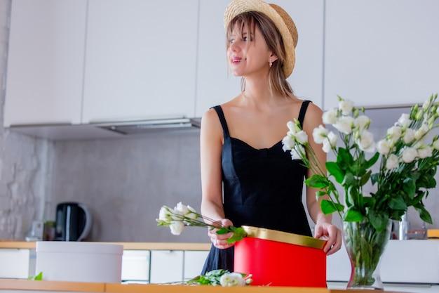 Mulher perto de buquê de rosas brancas em um vaso e caixa de presente