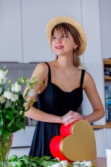 Mulher perto de buquê de rosas brancas em uma caixa de vaso e presente