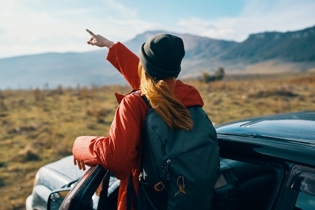 Mulher perto de carros, gesticulando com as mãos sobre a natureza nas montanhas, turismo de viagens de mochila de outono