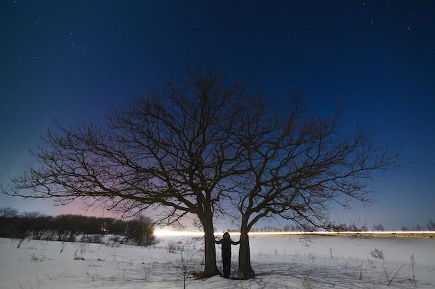 Mulher perto de uma árvore num contexto de um céu estrelado à noite no inverno.