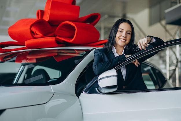 Mulher perto do carro com grande laço vermelho