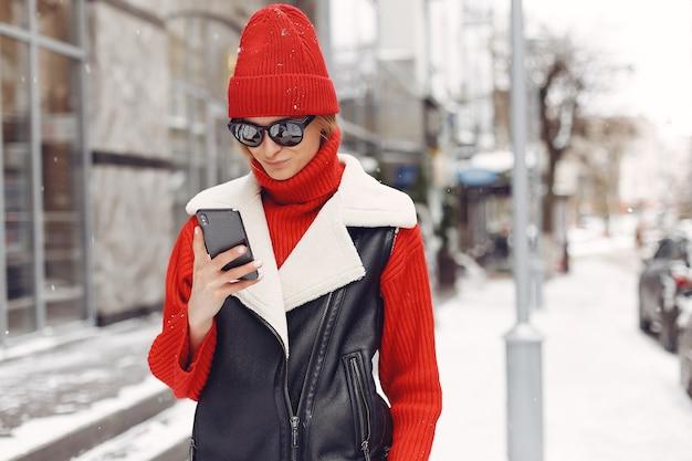 Mulher perto do prédio. humor de ano novo. senhora com uma jaqueta preta.