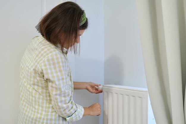 Mulher perto do radiador de aquecimento, regula a temperatura com o regulador do termostato