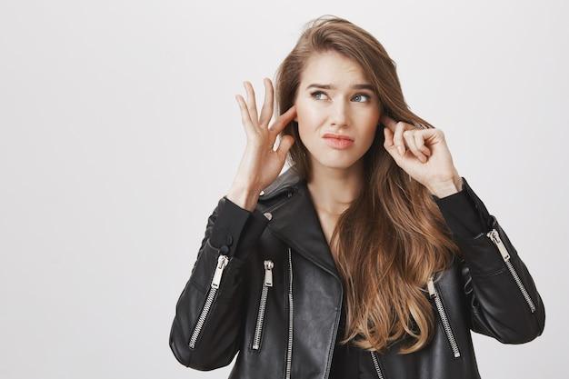 Mulher perturbada perto dos ouvidos com os dedos por causa do barulho alto