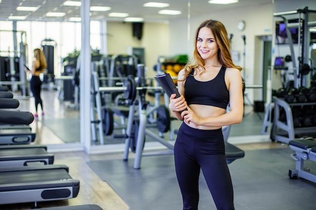 Mulher pessoal do instrutor que guarda a prancheta com plano de formação no gym.