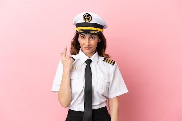 Mulher piloto de avião de meia-idade isolada em fundo rosa apontando com o dedo indicador uma ótima ideia