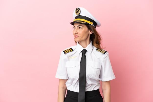 Mulher piloto de avião de meia-idade isolada em fundo rosa olhando de lado